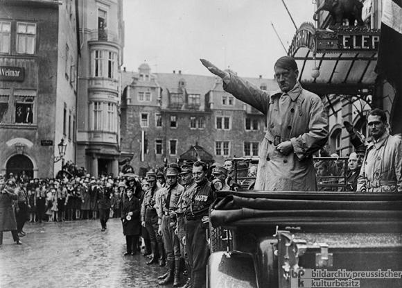 Rechts neben ihm im Auto Rudolf Heß. Vor dem Wagen Hermann Göring, Freiherr von Killinger, Fritz Sauckel.Aufnahmedatum: 12.10.1930Aufnahmeort: WeimarSystematik: Geschichte / Deutschland / 20. Jh. / NS-Bewegung / Aufmärsche und Treffen / 1930 / Deutscher Tag in Weimar