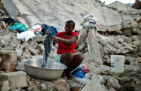 A woman washes clothes in Port-au-Prince Jan. 11 next to a house destroyed by the Jan. 12, 2010, earthquake that devastated Haiti. As more and more Haitians seek the knowledge and skills to make their own decisions on rebuilding the country, international aid and development agencies have begun to involve local communities in planning for the delivery of services. (CNS photo/Kena Betancur, Reuters) (Jan. 12, 2011) See HAITI-RECOVERY Jan. 12, 2011.